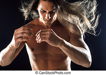 muscular man with long hair, clasps hands in fist, black...