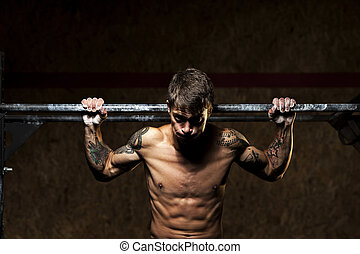 Muscular man with naked torso doing pull up in gym