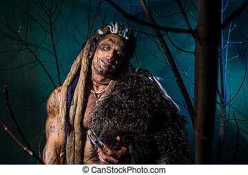 Muscular man with skin and dreadlocks among the trees