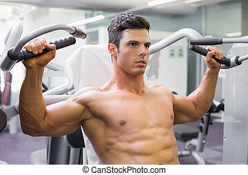 Muscular man working on fitness machine at the gym -...