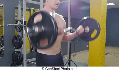 Muscular man working out in gym doing exercises with barbell at biceps