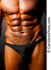 muscular man's body on black background