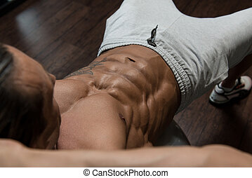 Exercising Abdominals On Exercise Ball - Muscular Mature Man...