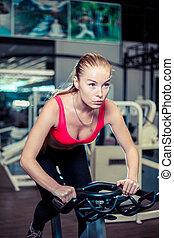 muscular, mulher jovem, trabalhar, ligado, a, bicicleta exercício, em, a, ginásio, intenso, cardio, workout.