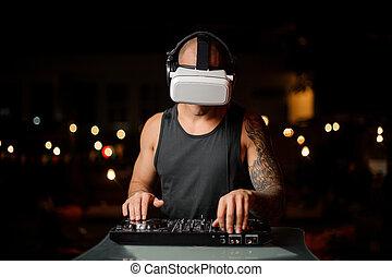 Muscular nightclub DJ in night vision glasses