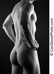Muscular nude man - Young muscular sporty man over black...