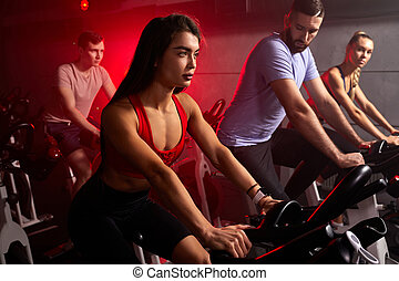 muscular people in gym, perfect shaped muscular people training on bicycle