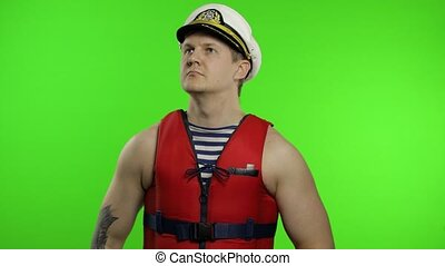 Young muscular sailor man works as lifeguard at beach salutes with hand to camera. Seaman guy life saver in sailor's vest, lifejacket, captain nautical hat. Isolated on chroma key background