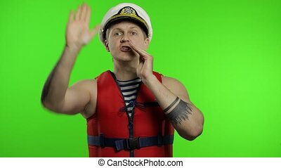 Young muscular sailor man works as lifeguard at beach shouts someone, reports the danger. Seaman guy life saver in sailor's vest, lifejacket, captain nautical hat. Isolated on chroma key background