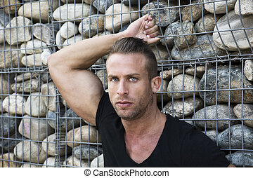 Muscular sexy man in front of stone wall, looking at camera