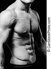 Muscular sexy torso of young sporty man with perfect abs close up. Black and white isolated on black background