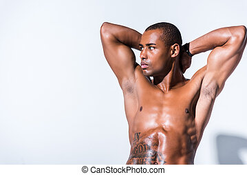 muscular shirtless african american sportsman with hands behind head looking away isolated on grey
