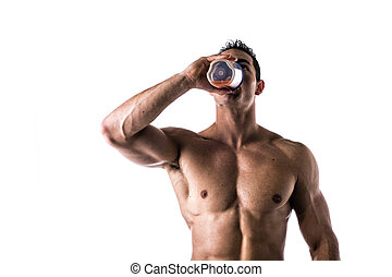 Muscular shirtless male bodybuilder drinking protein shake...