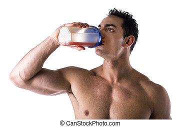 Muscular shirtless male bodybuilder drinking protein shake from blender