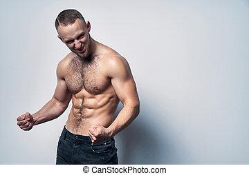 Muscular shirtless man celebrating success screaming -...