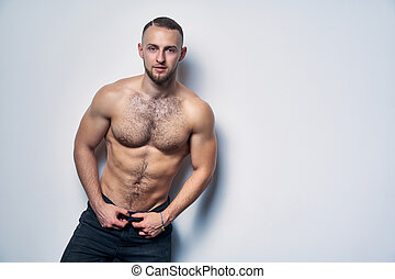Muscular shirtless man in jeans standing at white wall looking at camera