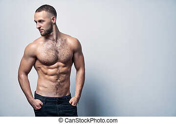 Muscular shirtless man in jeans standing at white wall