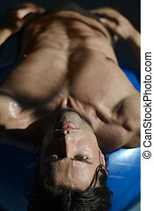 Muscular shirtless man laying down, belly up looking at...