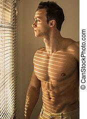 Muscular shirtless man lit by sun behind venetian blinds,...
