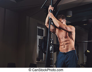 Muscular shirtless man posing with a barbell in the gym.