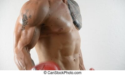Muscular shirtless young man exercising with dumbbells