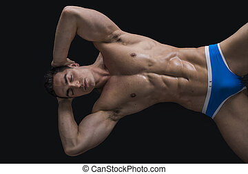 Muscular shirtless young man laying on the floor