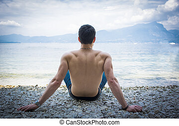 Muscular shirtless young man on lake in a sunny, peaceful