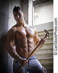 Muscular shirtless young man with farming tool