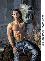 Muscular shirtless young man working. Carrying canister on shoulder