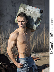 Muscular shirtless young man working. Carrying plastic...