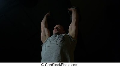 Muscular sports man is engaged in training cross fit in the gym ,the concept of sport. Attractive muscular bodybuilder guy prepare to do exercises in a gym. kettlebell rocking