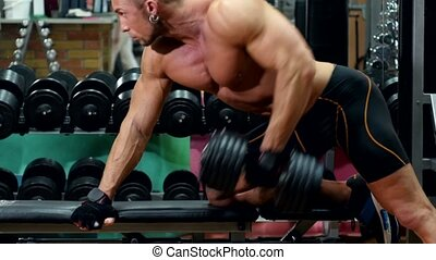 Muscular sportsman doing exercises on left hand with dumbbell in the gym