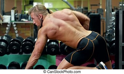 Muscular sportsman doing exercises on right hand with dumbbell in the gym