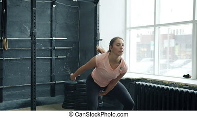 Muscular sportswoman training with kettlebell squatting and ...