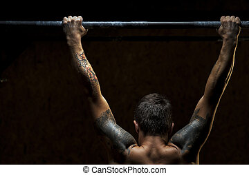 Muscular strong man doing pull ups on bar