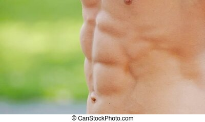Muscular strong man moving his abdominal muscles, slow...