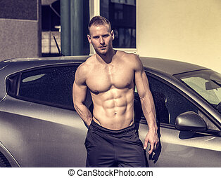 Muscular topless man outside of car