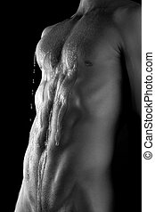 Muscular torso with waterdrops over black background