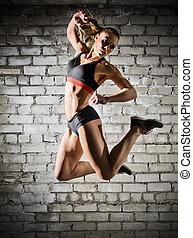 Muscular woman on brick wall (dark version) - Muscular woman...
