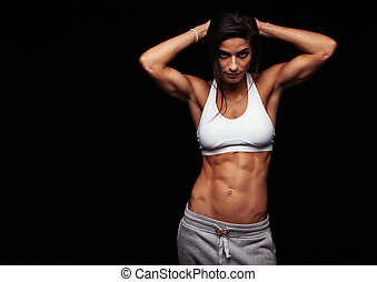 Muscular woman posing in fitness clothing
