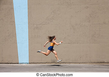 Muscular woman sprints to win - Woman sprinter practices her...