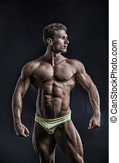 Muscular young bodybuilder in relaxed pose, smiling