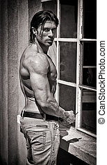 Muscular young bodybuilder shirtless outdoors in jeans -...