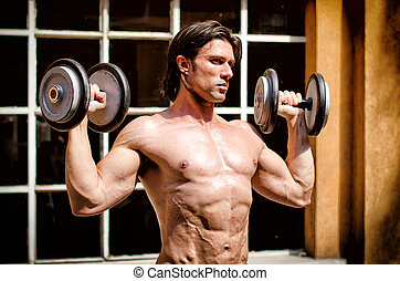 Muscular young bodybuilder shirtless with dumbbells