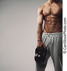 Muscular young guy with kettle bell - Cropped image of young...