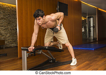 Muscular young male athlete working out in gym, exercising triceps