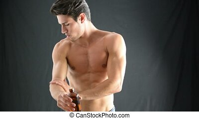 Muscular Young Man Applying Oil to his Skin