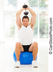 young man at the gym exercising with dumbbell