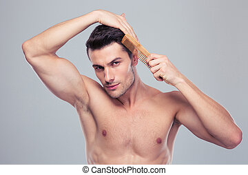 Portrait Of A Young Man Combing His Hair With Hair Comb