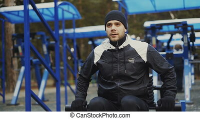 Muscular young man doing exercise in outdoor gym in winter park